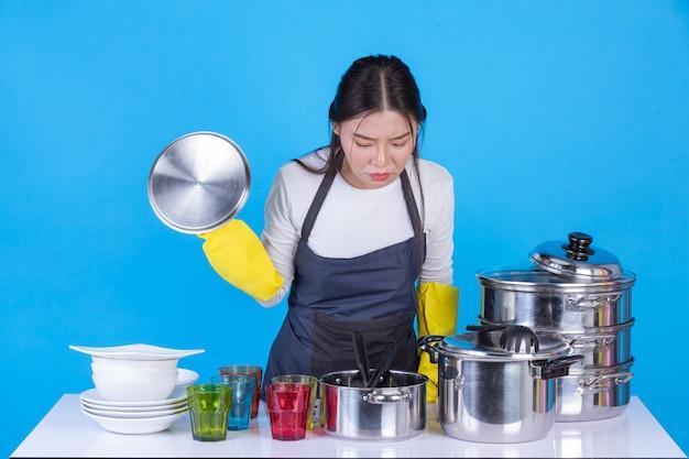 Красивая женщина моет посуду перед ним на синем.