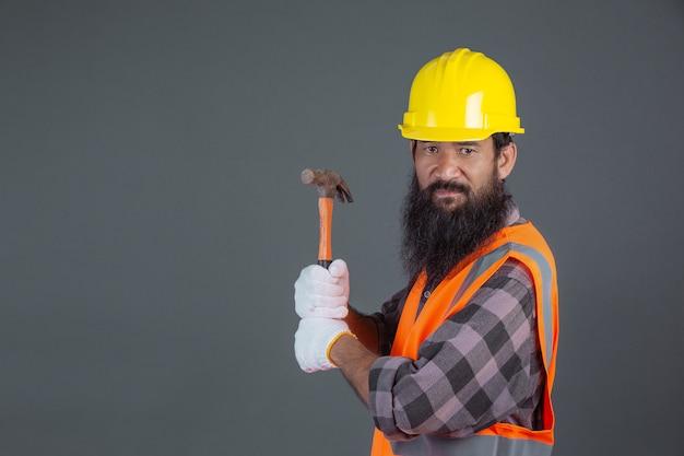 Человек инженерства нося желтый шлем с строительным оборудованием на сером цвете.