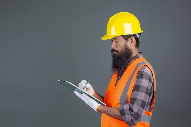 Человек инженерства нося желтый шлем с дизайном на сером цвете.