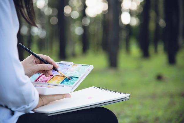 緑の庭の森の自然の中で女性の絵画水彩アート作品をリラックスします。