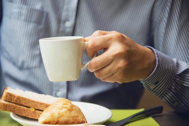 ビジネスの男性はホテルで設定されたアメリカン・ブレックファーストを食べる