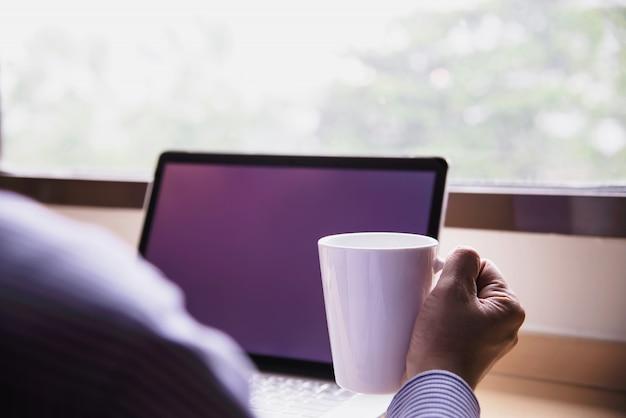 ホテルの部屋でコーヒーカップを持つコンピューターでの作業の実業家