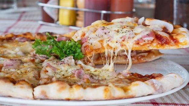 Семейный обед, съедая пиццу с ветчиной и сыром