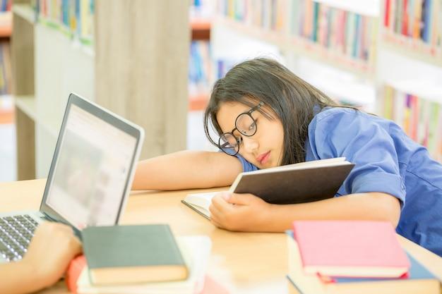 メガネの若い茶色の髪の女性は本を読む