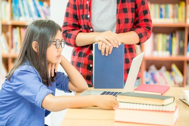 学校の図書館で勉強している学生