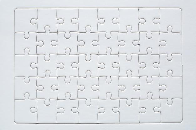 白いジグソーパズルのピースと未完成の赤