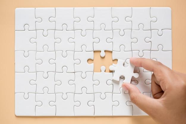 テーブルの背景にパズルのピースを接続する手