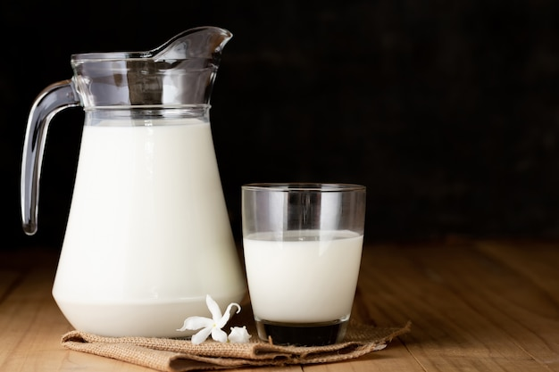 ガラスと木製のテーブルの水差しのミルク