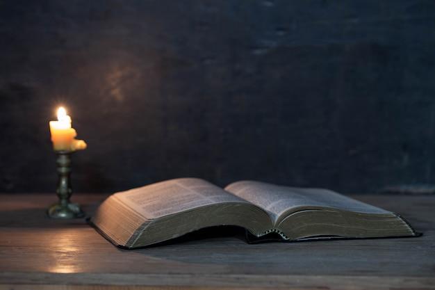 Священные писания и свечи на деревянном столе