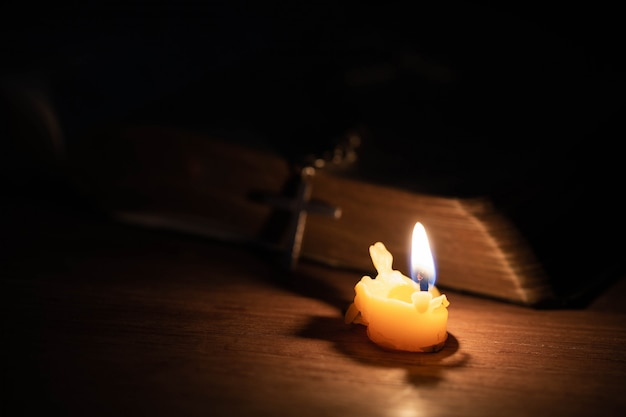 古いオークの木製テーブルの上の聖書とキャンドルを渡ります。