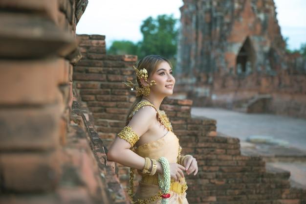 タイの古い伝統的な衣装、古代アユタヤ寺院の肖像画で美しい女性