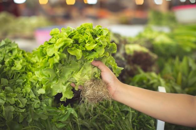 Женщина покупает органические овощи