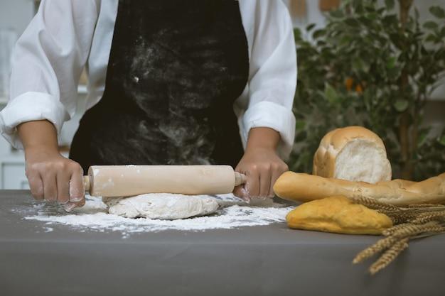 男性のパン屋は小麦粉でパンを準備します