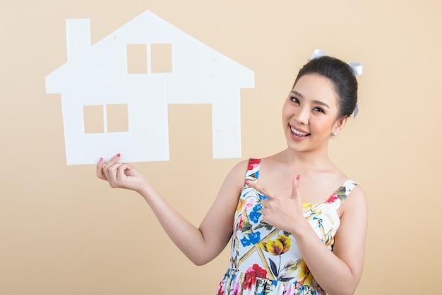 紙の家を保持している若い幸せな興奮したアジア女性の肖像画