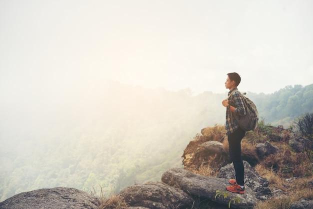 山の頂上にバックパック付きの旅行者。旅行のライフスタイルの概念。