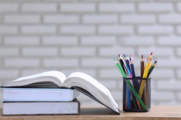 机の上の本と鉛筆の山