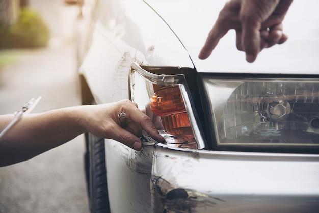 現場での自動車事故請求プロセス中に働く保険代理店、人と車の保険請求