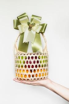 Рука показывает сувенир из свежих фруктов в плетеной бамбуковой упаковке на белом сером