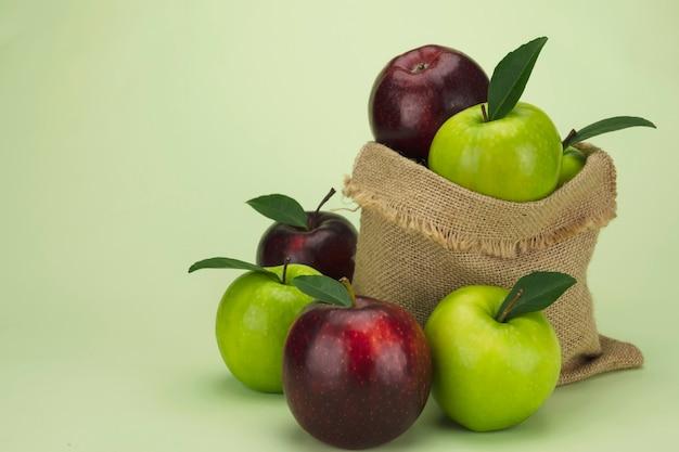 Свежее красное яблоко на мягких зеленых, свежих фруктах