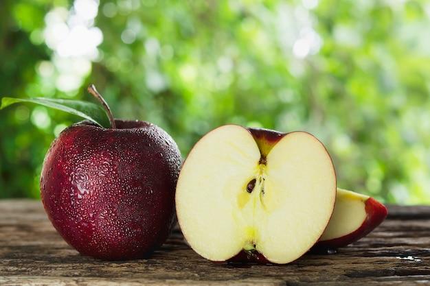 Свежее яблоко с каплей воды на коже над зеленой природой, свежие фрукты