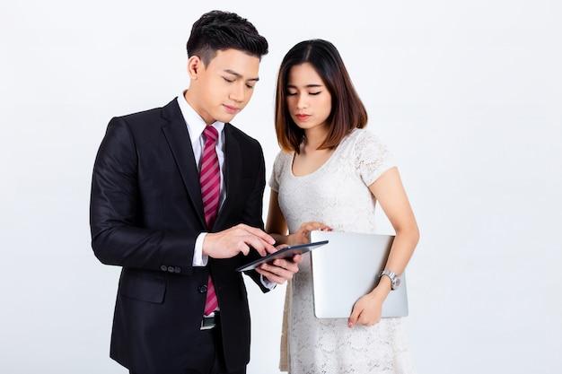 Два бизнесмены обсуждают и используют планшет на белом