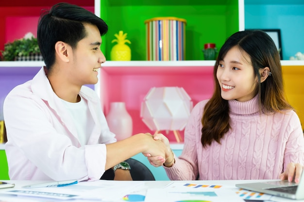 Красивая женщина, рукопожатие с молодым человеком