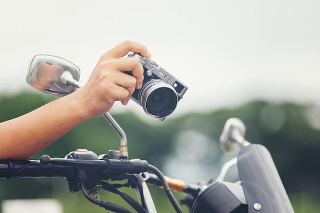 若いアジア男性旅行者とカメラを保持しているクラシックなスタイルのレーサーバイクに座っている写真家