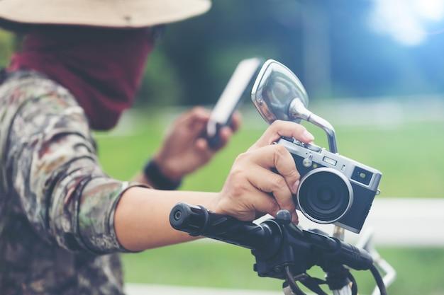 Молодой азиатский мужской путешественник и фотограф сидя на мотоцикле гонщика классического стиля держа камеру