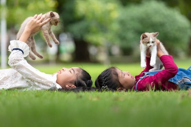 公園で子猫を保持しているアジアの若い女の子