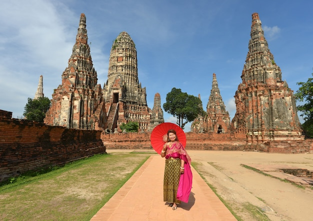 伝統的なタイのドレスで幸せな引退した女性は、寺院で旅行します。