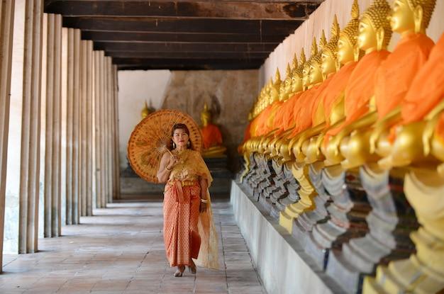 Счастливая пенсионерка в традиционном тайском платье путешествует в храме.