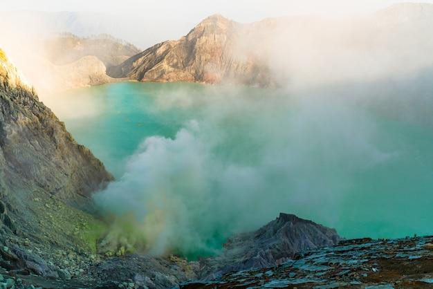 煙を吐き出す岩の多い風景の中にある湖