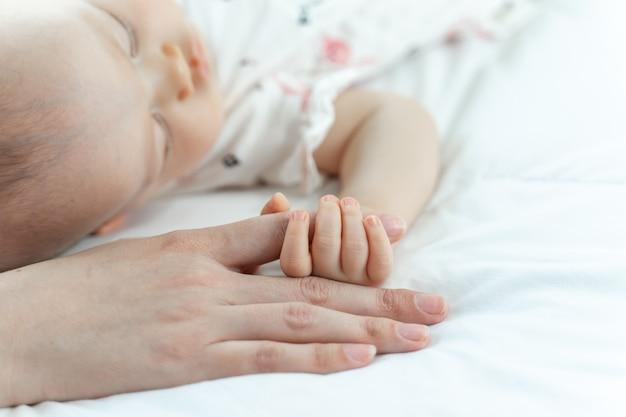 寝ている母親の指をつかんでいる赤ちゃん
