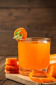木製のテーブルの上のガラスのにんじんジュース。