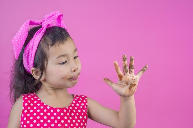 Милая девушка в красной полосатой рубашке ест шоколад с грязным ртом на розовый.