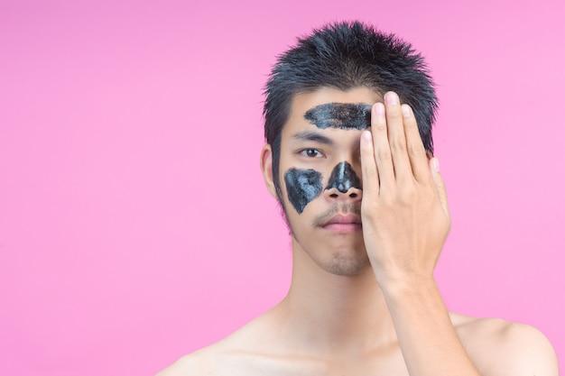 手で顔の半分を隠す男性は、黒い化粧品とピンクの化粧品を持っています。