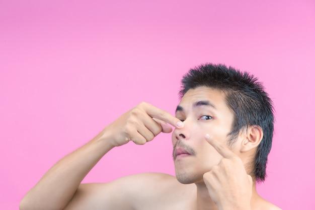 Молодой человек, используя его руки, чтобы сжать прыщи на лице и розовый.