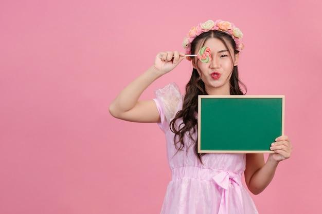 Красивые женщины, одетые в розовые платья принцессы, держат зеленую доску на розовом.