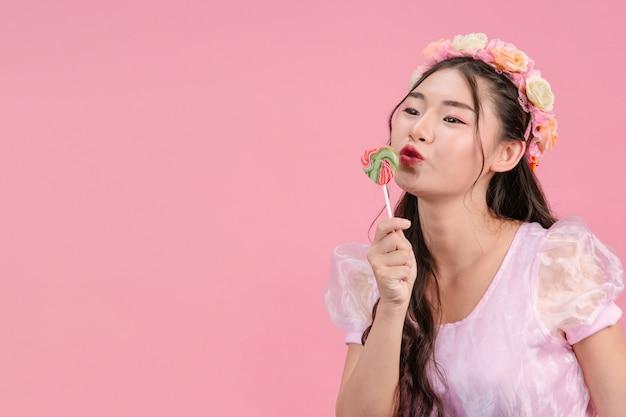 Красивая женщина в розовой принцессе играет со своей сладкой конфеткой на розовом.