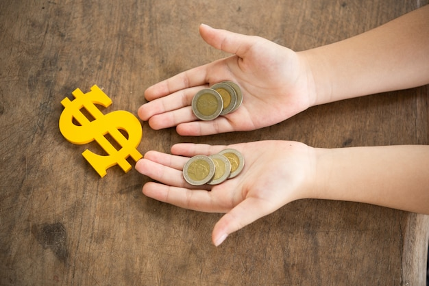 Ребенок держит монеты и желтый знак доллара