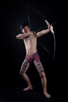 弓で戦う姿勢でポーズをとって若いタイ男性戦士