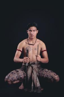剣との戦いの姿勢でポーズをとって若いタイ男性戦士