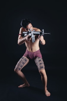 銃器との戦いの姿勢でポーズをとって若いタイ男性戦士