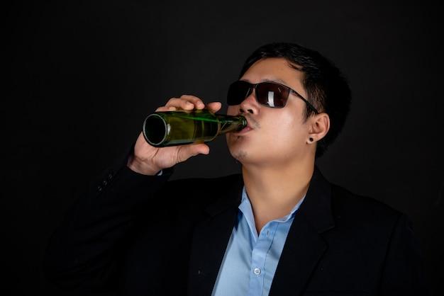 暗いジャケットとサングラスビール瓶を飲む男