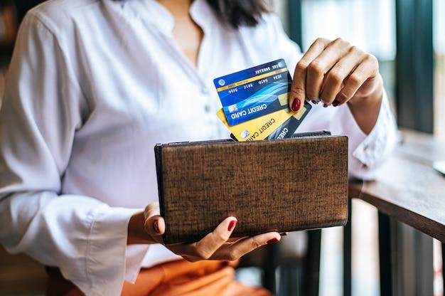 商品代金を支払うために茶色の財布からクレジットカードを受け取る