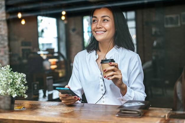 カフェでスマートフォンを介してクレジットカードでコーヒー代を支払う