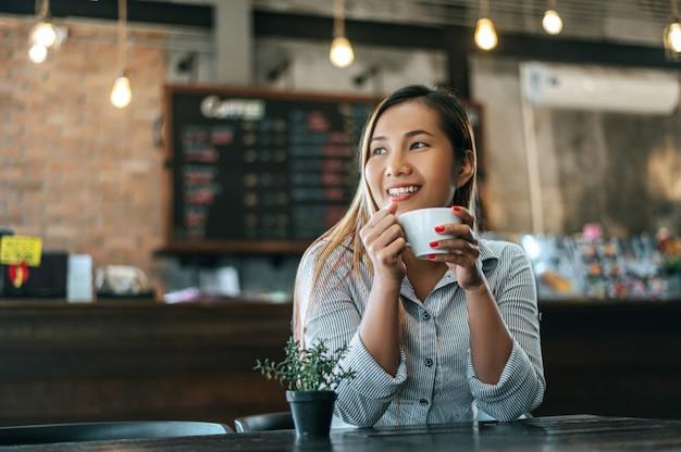 Женщина сидит счастливо пьет кофе в кафе