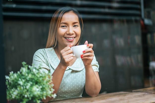 若い女性は喜んでカフェでコーヒーを飲みます