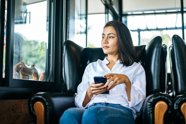 彼女の手でスマートフォンで窓の外見ている女性