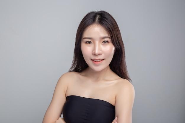 アジアの女性は黒いストラップレスのドレスを着て、幸せそうに笑った。
